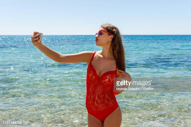 happy young woman taking selfie while standing at beach during summer - decote imagens e fotografias de stock