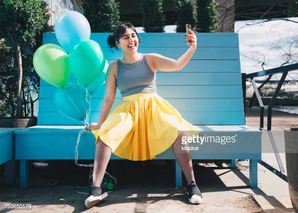 happy young woman taking selfie with balloons while sitting on bench - blue skirt stock pictures, royalty-free photos & images