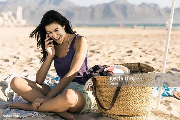 Happy young woman talking on phone at beach