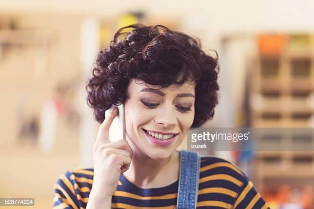 mulher jovem feliz um falar no telefone em um workshop de construção - izusek imagens e fotografias de stock