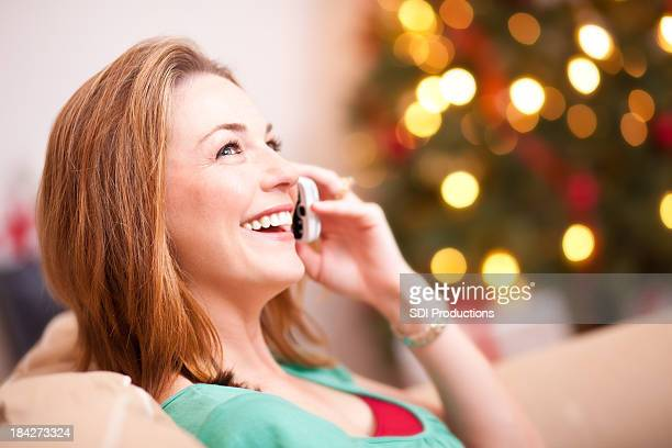 Happy Young Woman Talking on the phone at Christmas Time