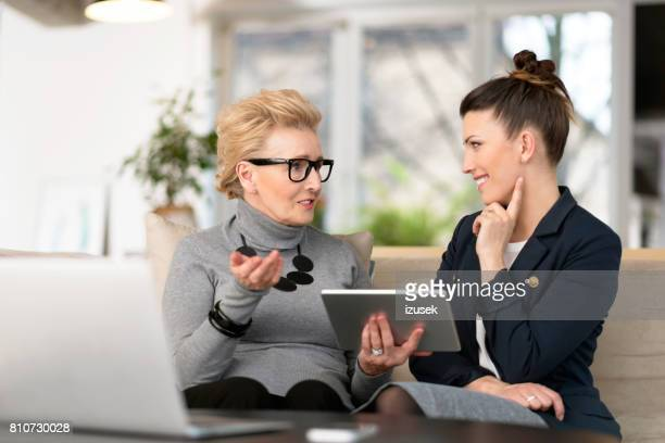 Happy young woman talking with her senior mentor