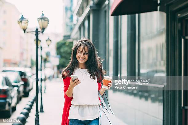 Happy young woman texting on the street