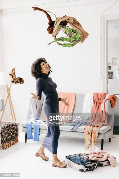 happy young woman throwing clothes into the air - throwing stock pictures, royalty-free photos & images
