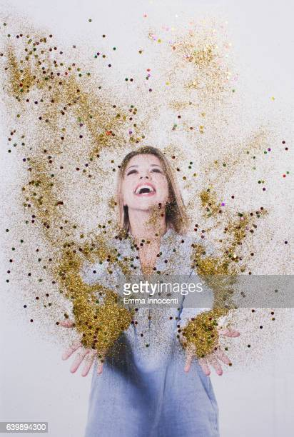 Happy young woman throwing up glitter
