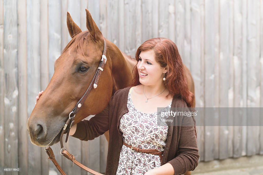 Happy young woman together with her brown horse : Stock Photo