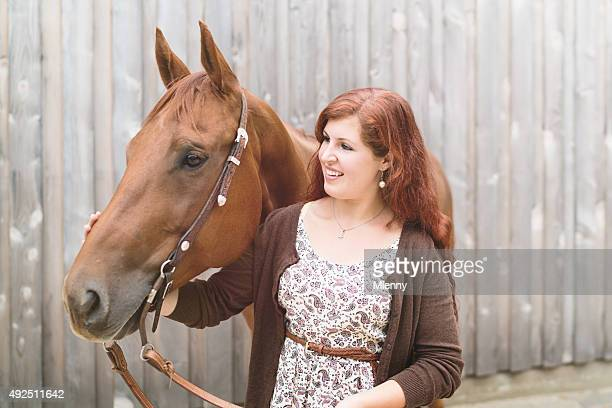 Happy young woman together with her brown horse