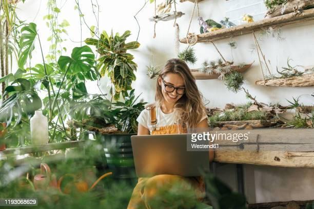 happy young woman using laptop in a small gardening shop - independência imagens e fotografias de stock