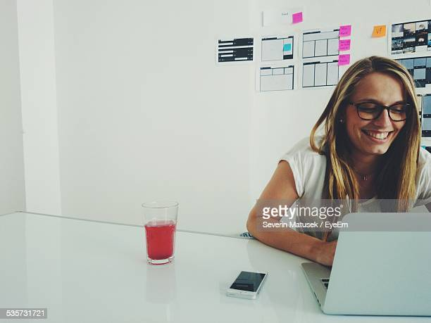 Happy Young Woman Using Laptop While Sitting On Desk