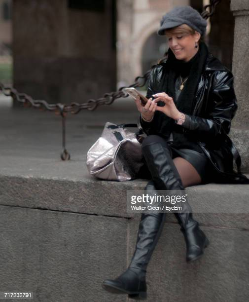happy young woman using mobile phone while sitting on stone wall - walter ciceri foto e immagini stock