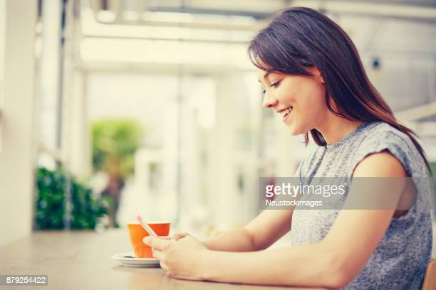 Happy young woman using smart phone at cafe