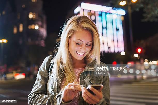 Happy young woman using smart phone on city street at night