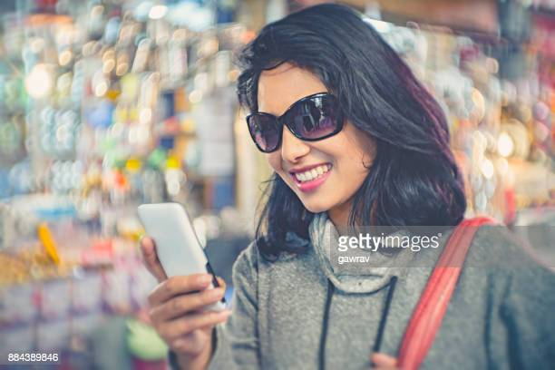 Happy young woman using smart phone.