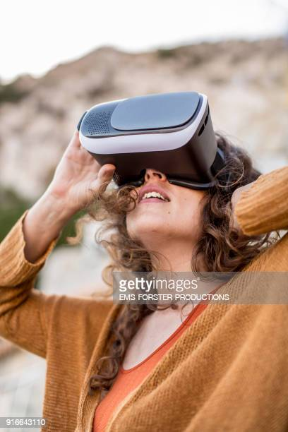 happy, young woman using virtual reality headset in the nature