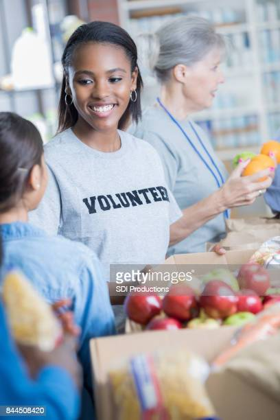 happy young woman volunteers in a food bank - altruism stock pictures, royalty-free photos & images
