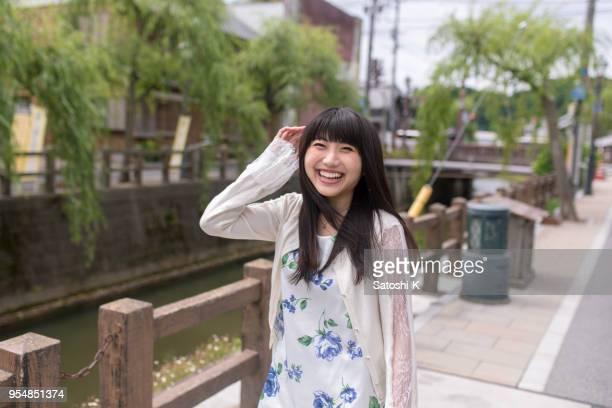 Happy young woman walking along river