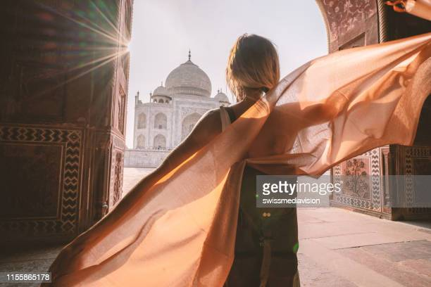 happy young woman walking and wandering at the famous taj mahal at sunrise holding scarf in hands, agra, india. people travel asia concept - sheer fabric stock pictures, royalty-free photos & images