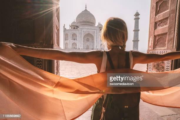 幸せな若い女性は、手にスカーフを持って日の出時に有名なタージマハルを歩いてさまよっています, アグラ, インド.人々はアジアの概念を旅する - アーグラ ストックフォトと画像