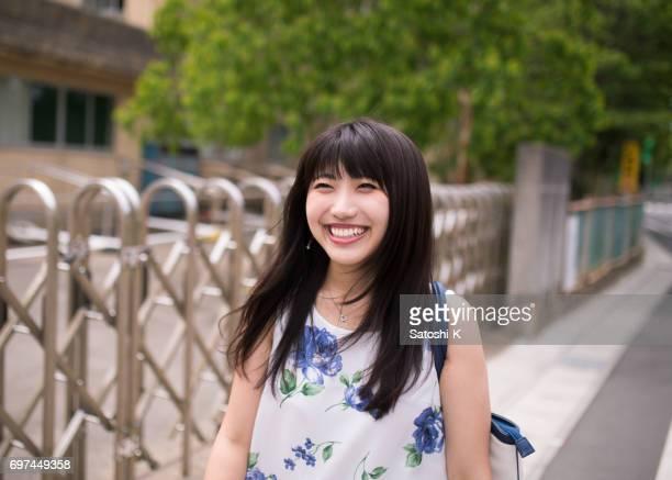 ローカルの住宅街の中を歩いて幸せな若い女