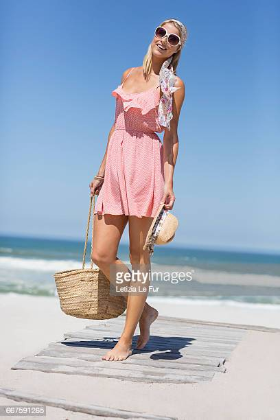 happy young woman walking on the beach - woman carrying tote bag stock photos and pictures