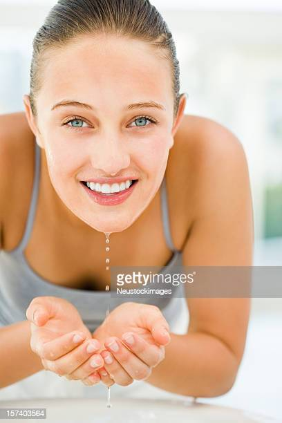 Happy young woman washing face with water