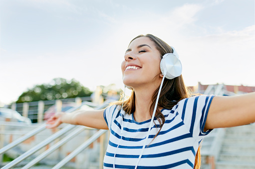 Happy young woman wearin headphones enjoying the summer - gettyimageskorea