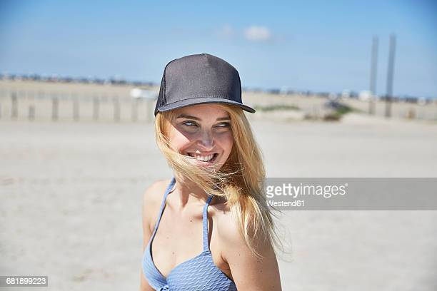 happy young woman wearing baseball cap on the beach - cap stock pictures, royalty-free photos & images