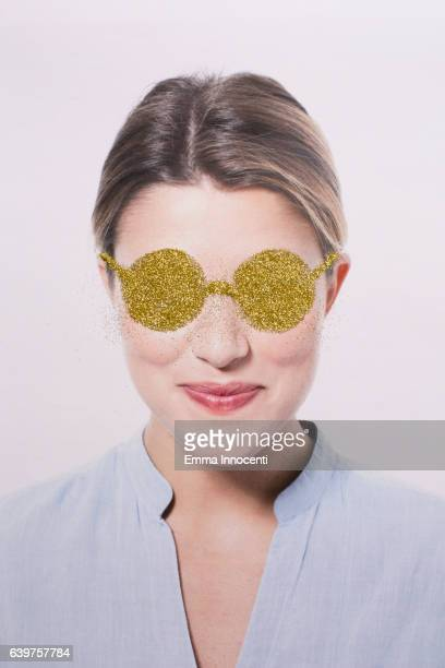 Happy young woman wearing gold glasses