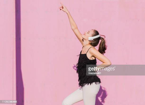 happy young woman wearing headphones dancing in front of pink wall - zuhören stock-fotos und bilder