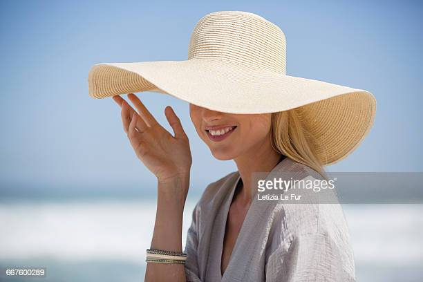 happy young woman wearing sunhat on beach - cappello foto e immagini stock
