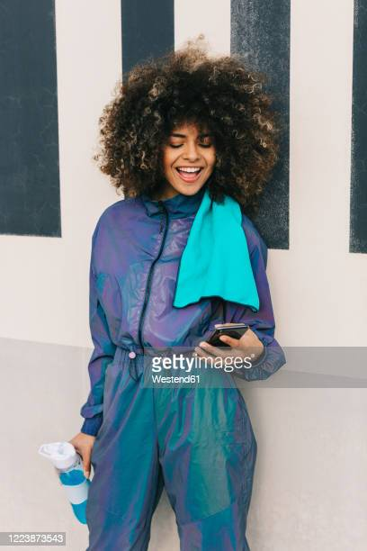 happy young woman wearing tracksuit and using cell phone outdoors - trainingsanzug stock-fotos und bilder