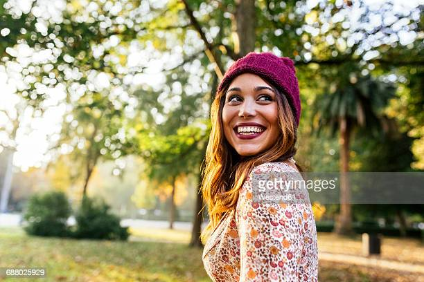happy young woman wearing wooly hat in a park in autumn - toothy smile stock pictures, royalty-free photos & images