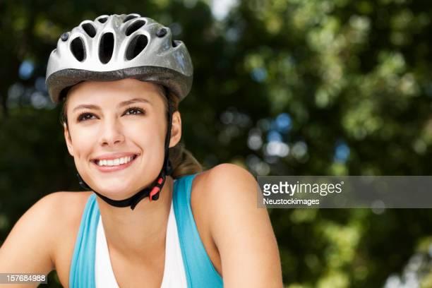 Happy young woman wears helmet on bike ride