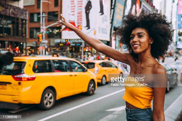 happy young woman with afro hairstyle hailing a ride on city street - off shoulder stock pictures, royalty-free photos & images