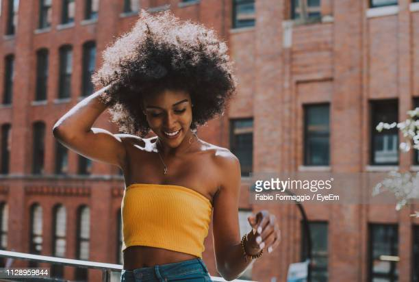happy young woman with afro hairstyle standing on bridge against building - off shoulder stock pictures, royalty-free photos & images