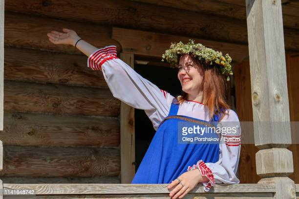happy young woman with arm raised standing by railing of house - hoofddeksel stockfoto's en -beelden
