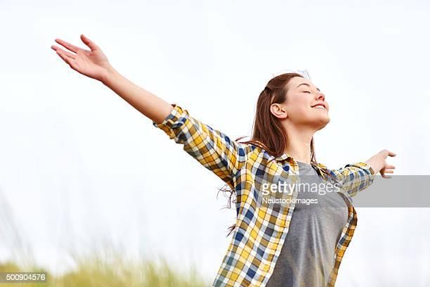 Heureuse jeune femme avec bras ouverts contre clair ciel