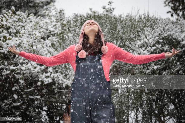 happy young woman with arms outstretched in snow - solo adulti foto e immagini stock