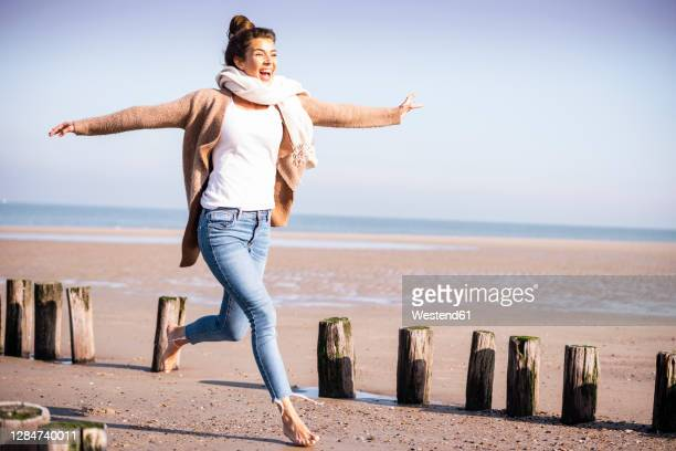 happy young woman with arms outstretched running amidst wooden posts at beach during sunny day - arms outstretched stock pictures, royalty-free photos & images