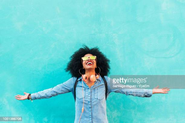 happy young woman with arms outstretched standing against blue wall - street style stock pictures, royalty-free photos & images