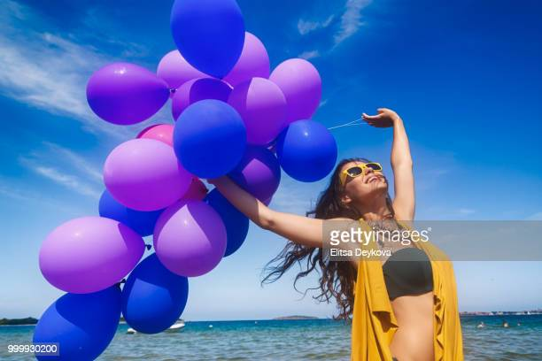 Happy young woman with balloons on the beach