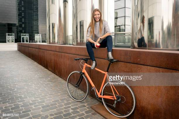 Happy young woman with bicycle having a break in the city eating an apple