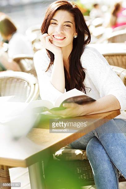 Happy young woman with book at a pavement cafe