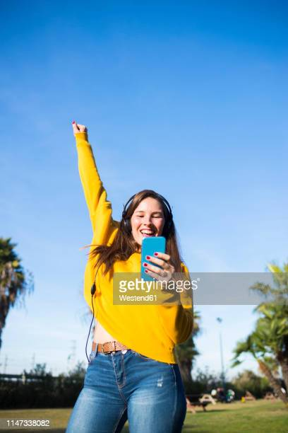 happy young woman with cell phone listening to music with headphones - vertical stock pictures, royalty-free photos & images