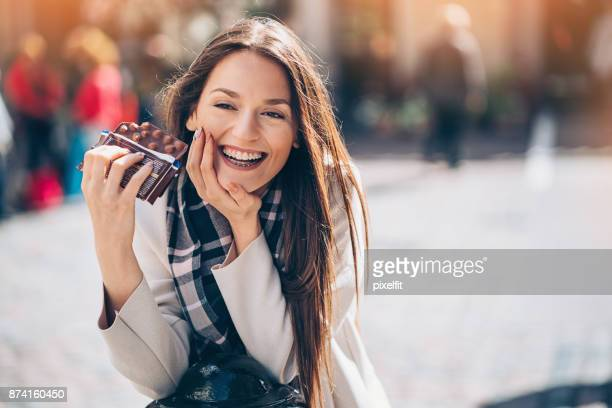 Happy young woman with chocolate bar