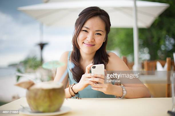 Happy young woman with coconut drink in tropical t