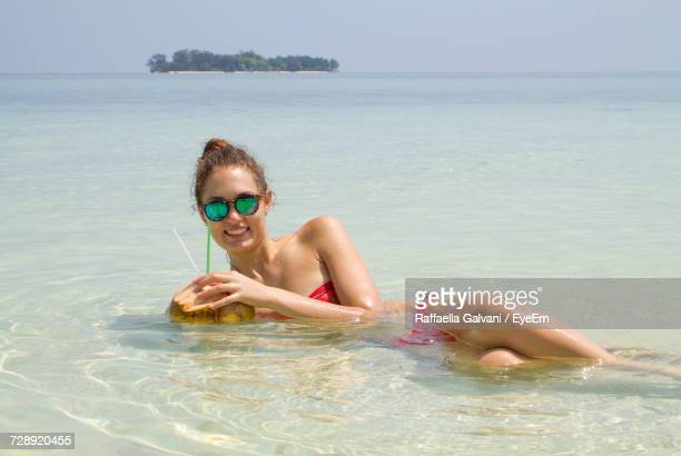 Happy Young Woman With Coconut Water Relaxing At Beach