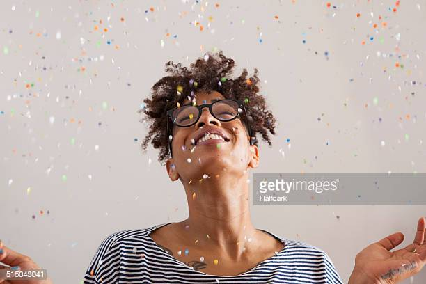 Happy young woman with confetti falling on her over gray background