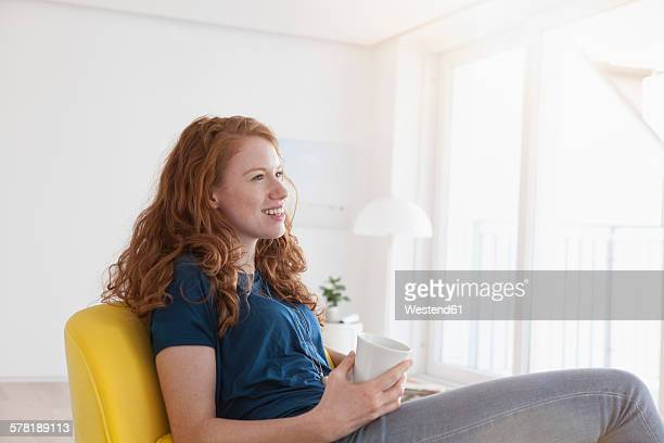 Happy young woman with cup of coffee sitting in her living room