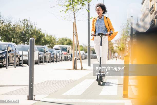 happy young woman with earphones riding e-scooter in the city - scooter stock pictures, royalty-free photos & images